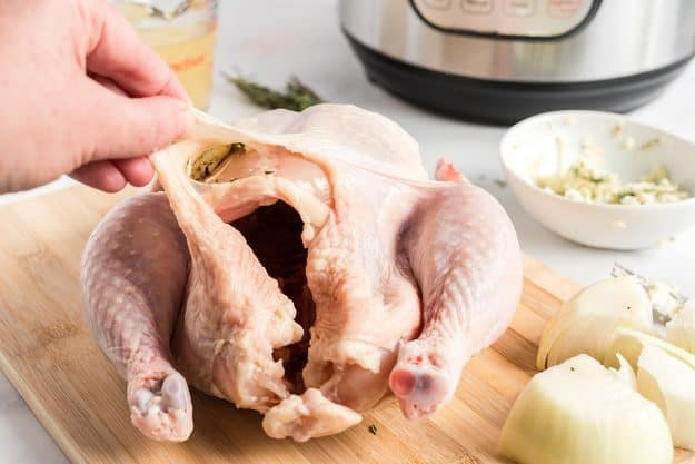 butter mixture being placed under the skin of chicken.