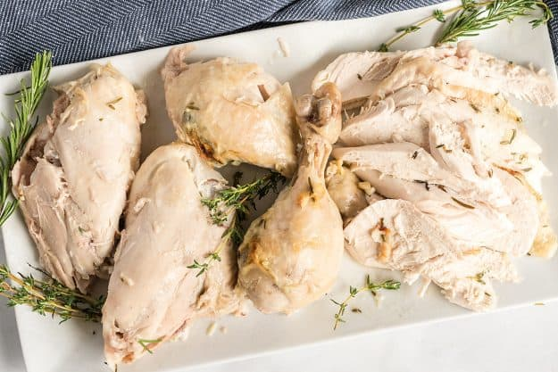 roasted chicken parts on white serving platter.