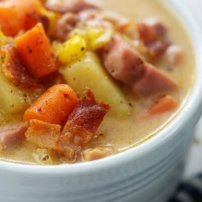 close up of ham and corn soup recipe in white bowl.