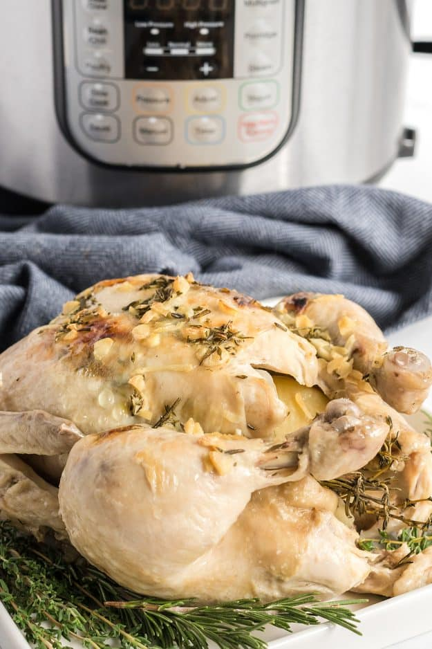 Instant Pot whole chicken on a bed of herbs.