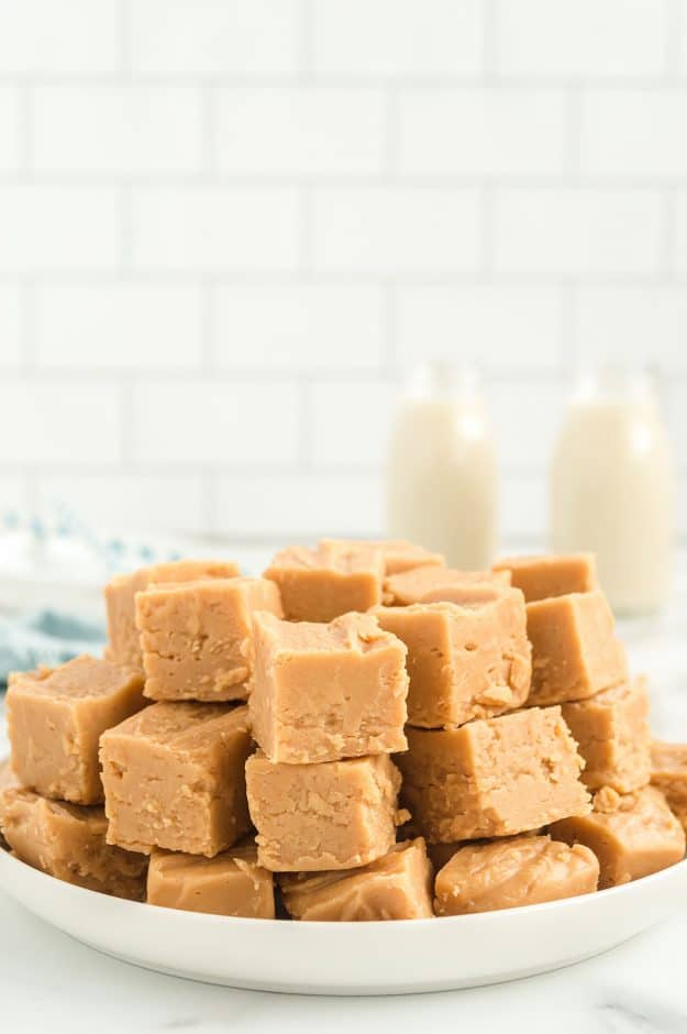 peanut butter fudge piled on white plate.