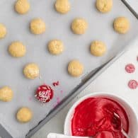cookie dough balls being dunked in red candy coating.