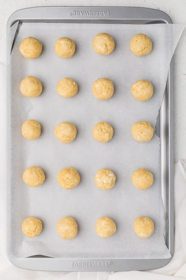 overhead view of cookie balls on baking sheet.