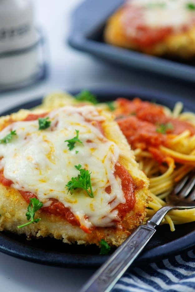 black plate topped with baked chicken parmesan and pile of pasta.