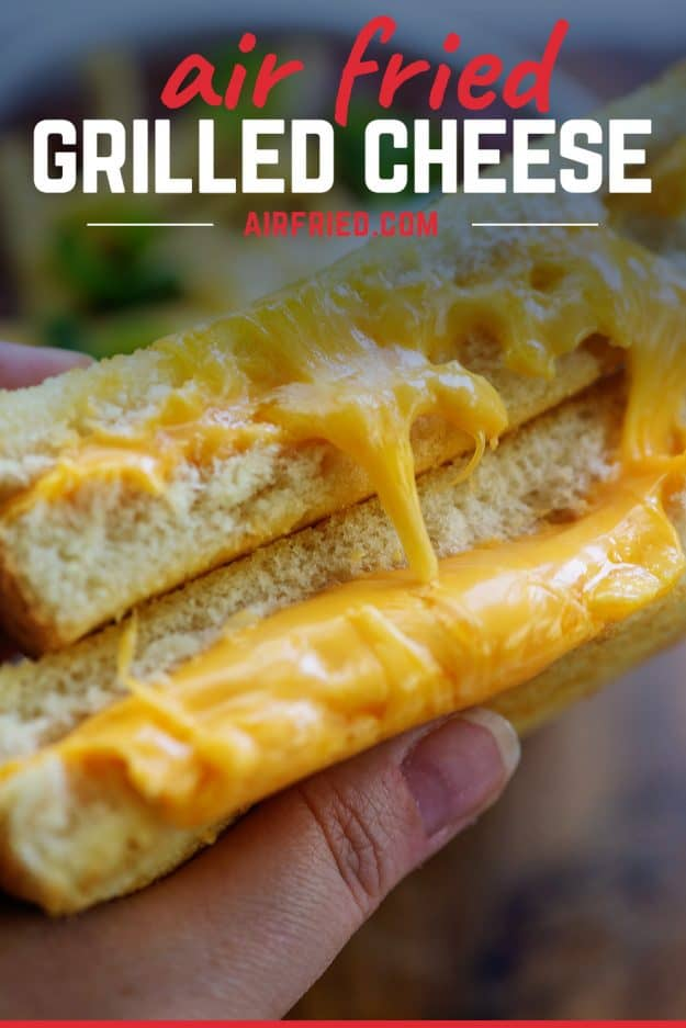 person holding an ultra cheesy grilled cheese sandwich.
