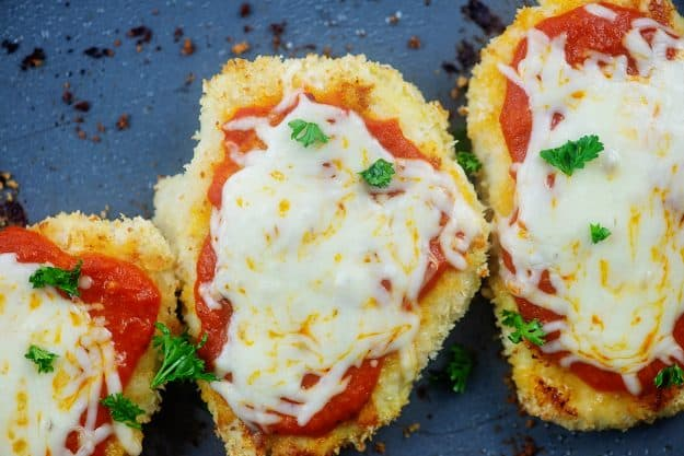 overhead view of easy chicken parmesan recipe on sheet pan.
