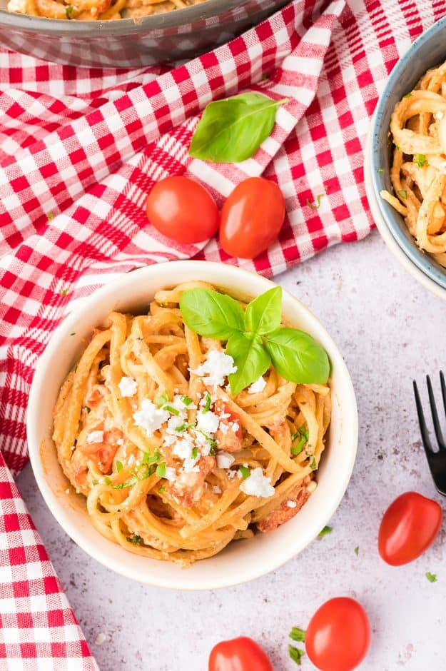 feta pasta in white bowl topped with extra feta crumbles.