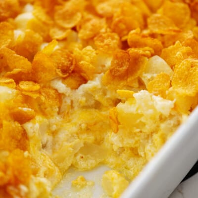 cheesy funeral potatoes in white baking dish.