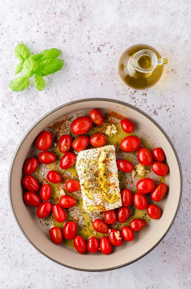 cherry tomatoes and feta cheese in baking dish.