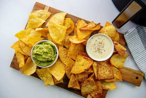 Homemade Doritos and tortilla chips on wooden board next to dip.