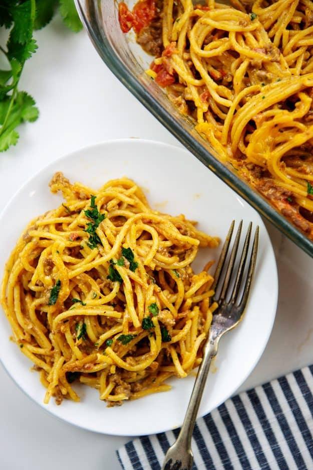 cheesy taco spaghetti bake on white plate.