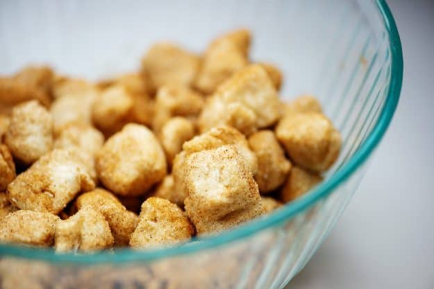 biscuits coated with cinnamon and sugar in glass mixing bowl.