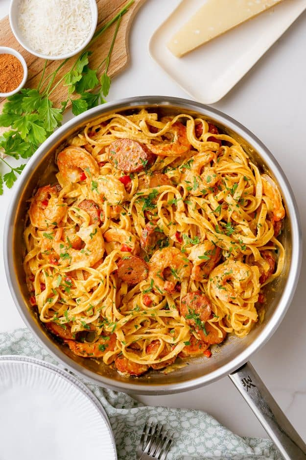 skillet filled with pasta, shrimp, and sausage.