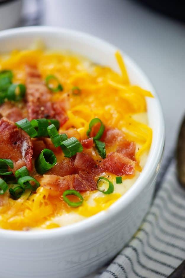 white bowl full of cheesy potato soup.