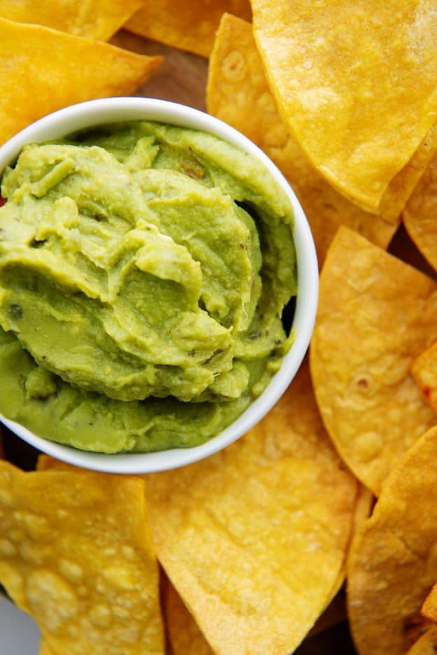 overhead view of air fryer tortilla chips next to a bowl of guacamole.