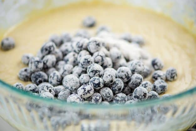 flour coated blueberries in glass mixing bowl.