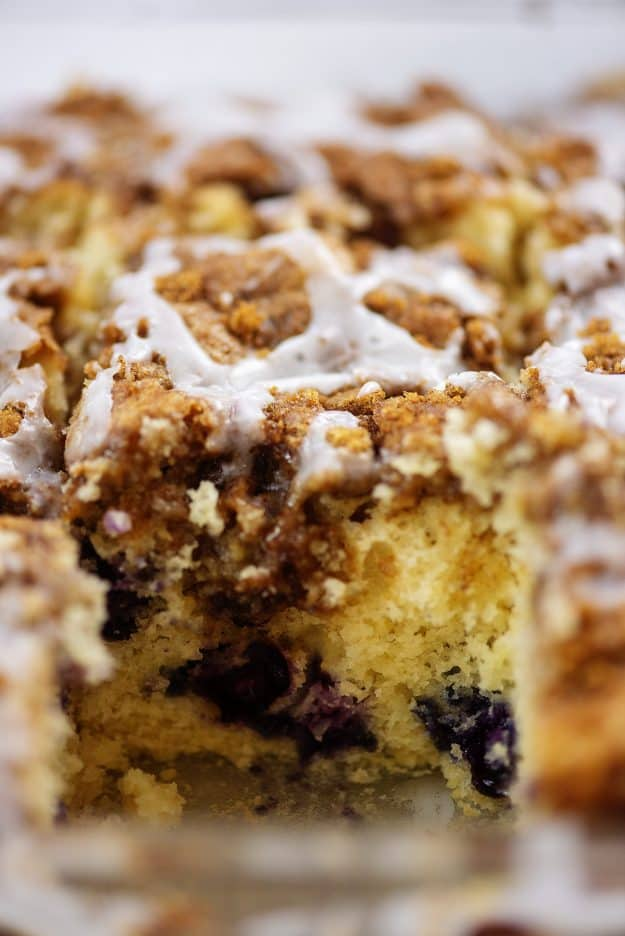 blueberry cinnamon roll breakfast cake with a slice taken out.