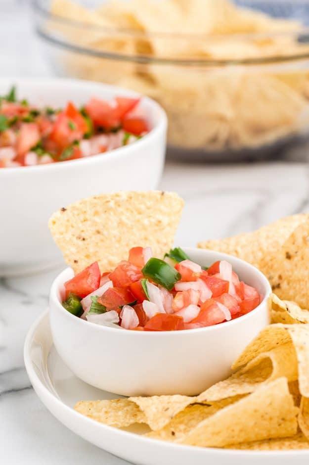 pico de gallo in white bowl with chips.