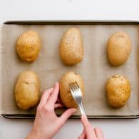 a woman poking holes in potatoes with a fork.
