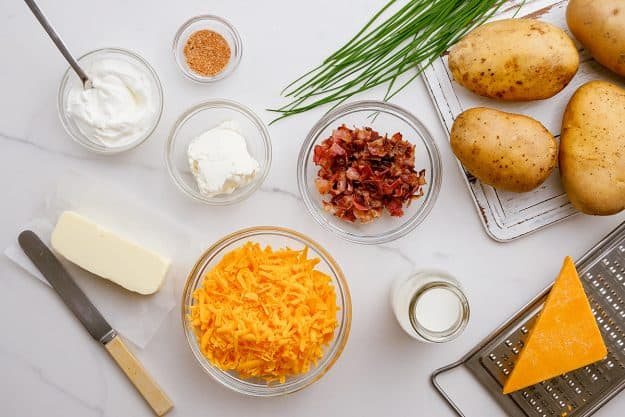 ingredients for twice baked potatoes on white counter.