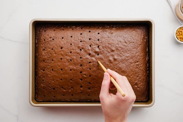 a woman using a skewer to poke holes in a chocolate cake.
