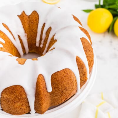 lemon bundt cake recipe on white cake stand.
