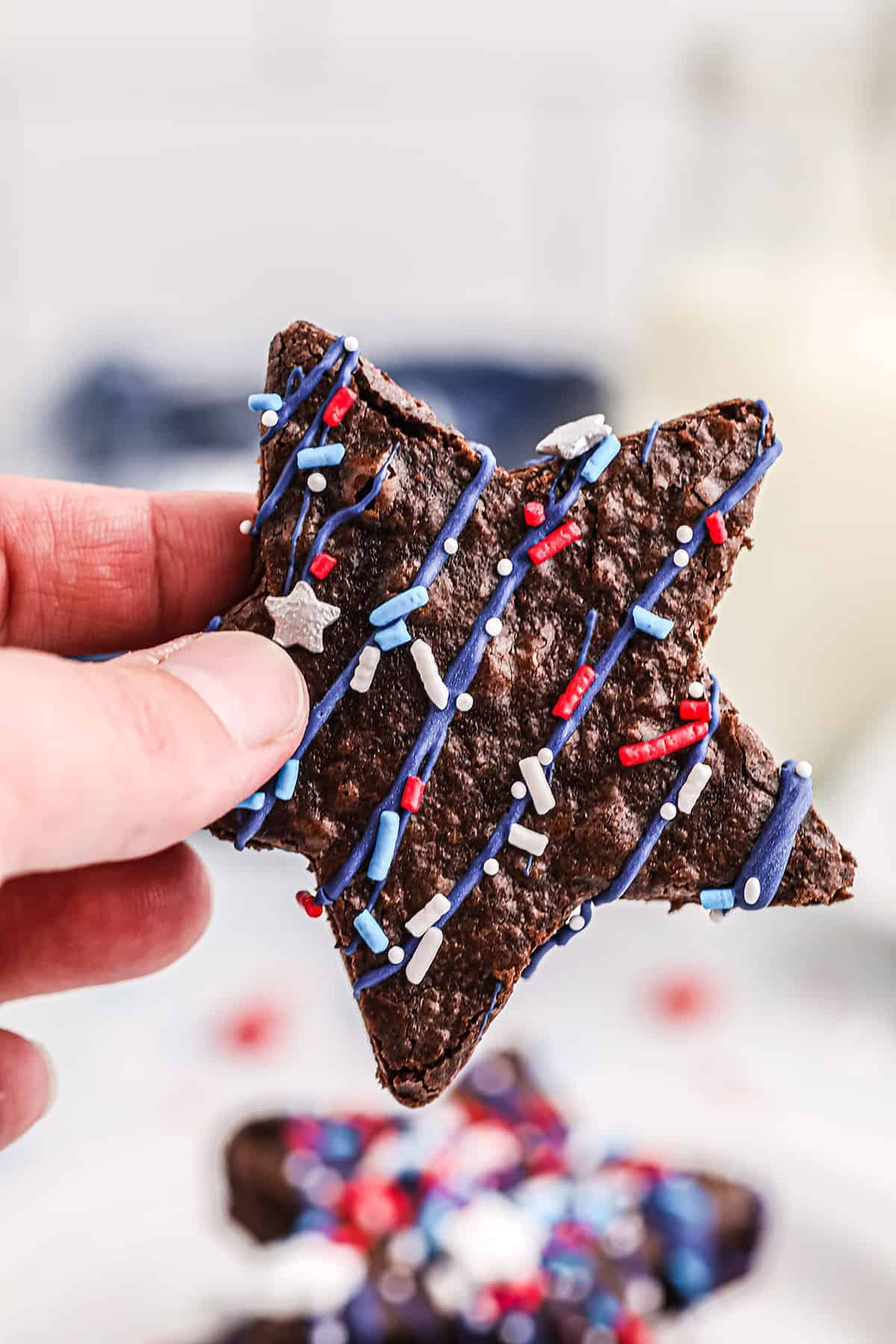 woman holding a star shaped brownie decorated for the Fourth of July.