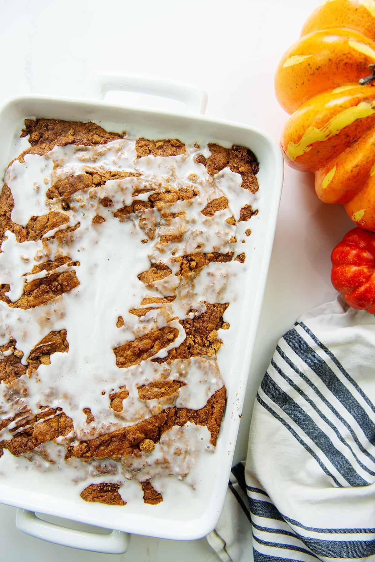 pumpkin cinnamon roll cake with glaze on top.