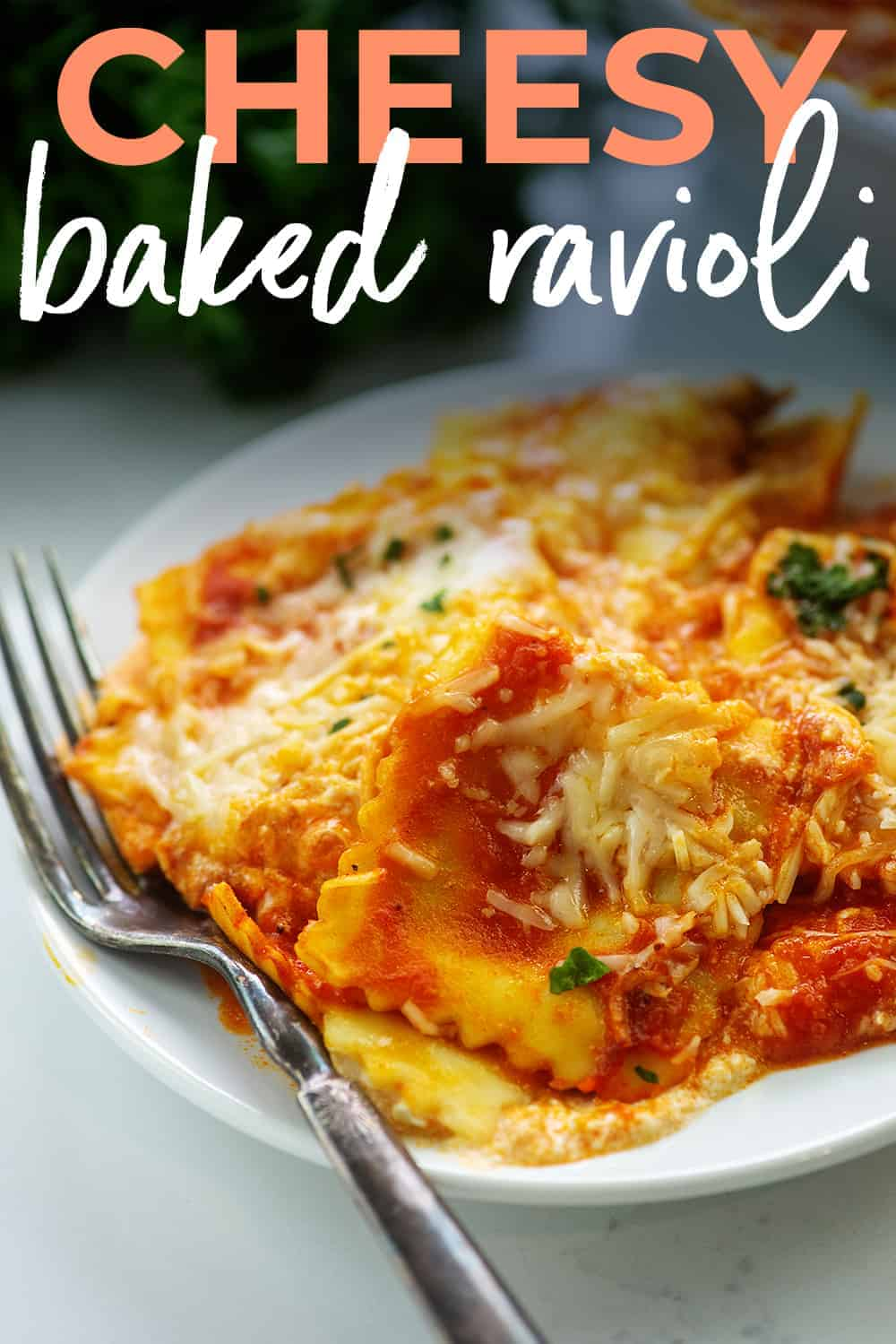 cheesy baked ravioli on white plate with text for Pinterest.