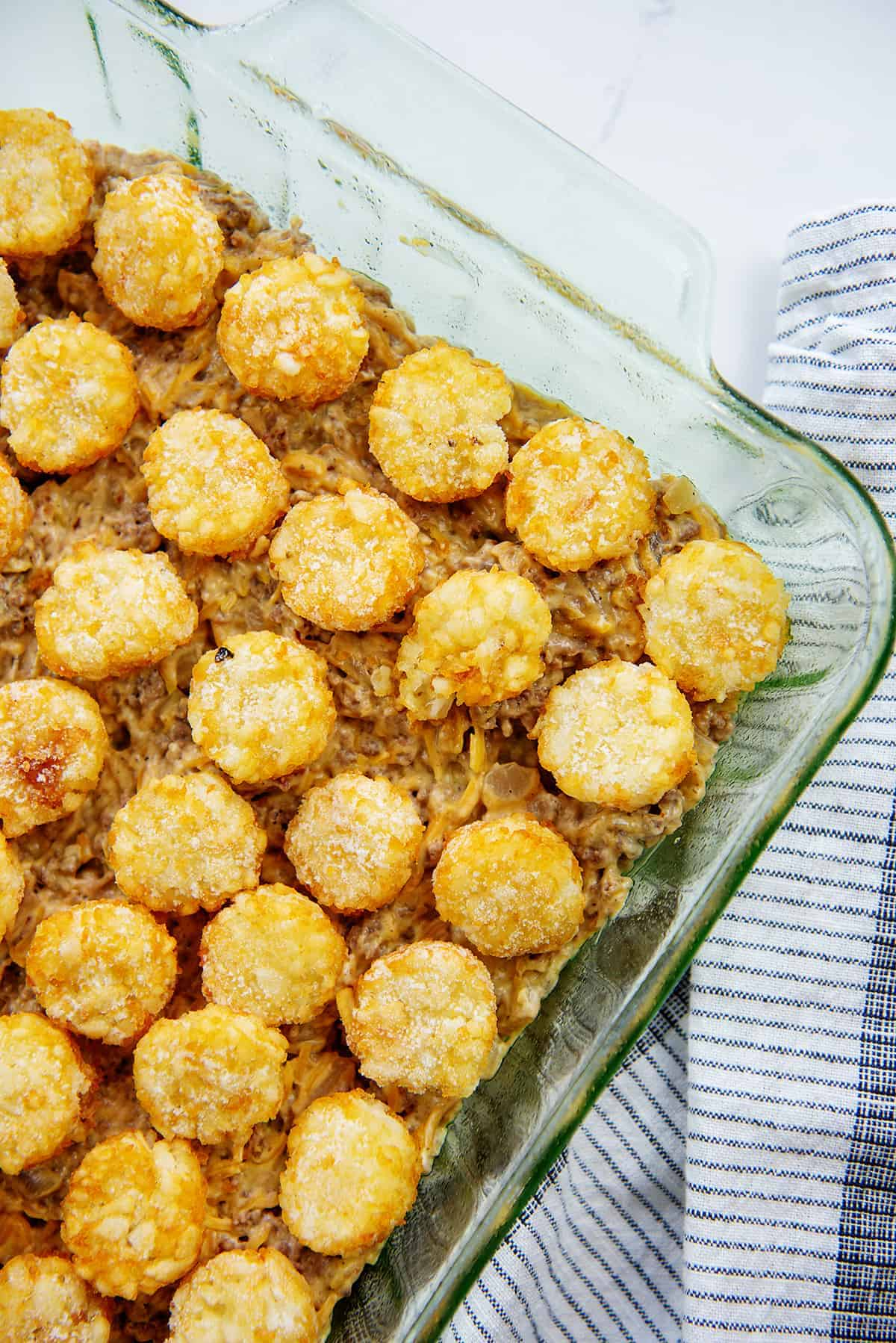 cheeseburger casserole topped with tater tots in glass baking dish.