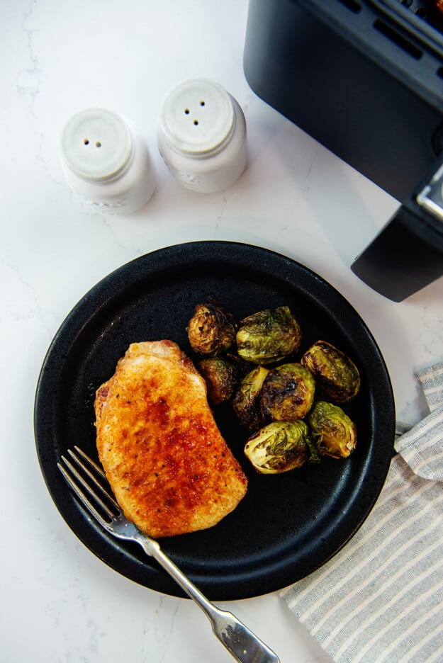 overhead view of pork chop and Brussels sprouts on black plate.