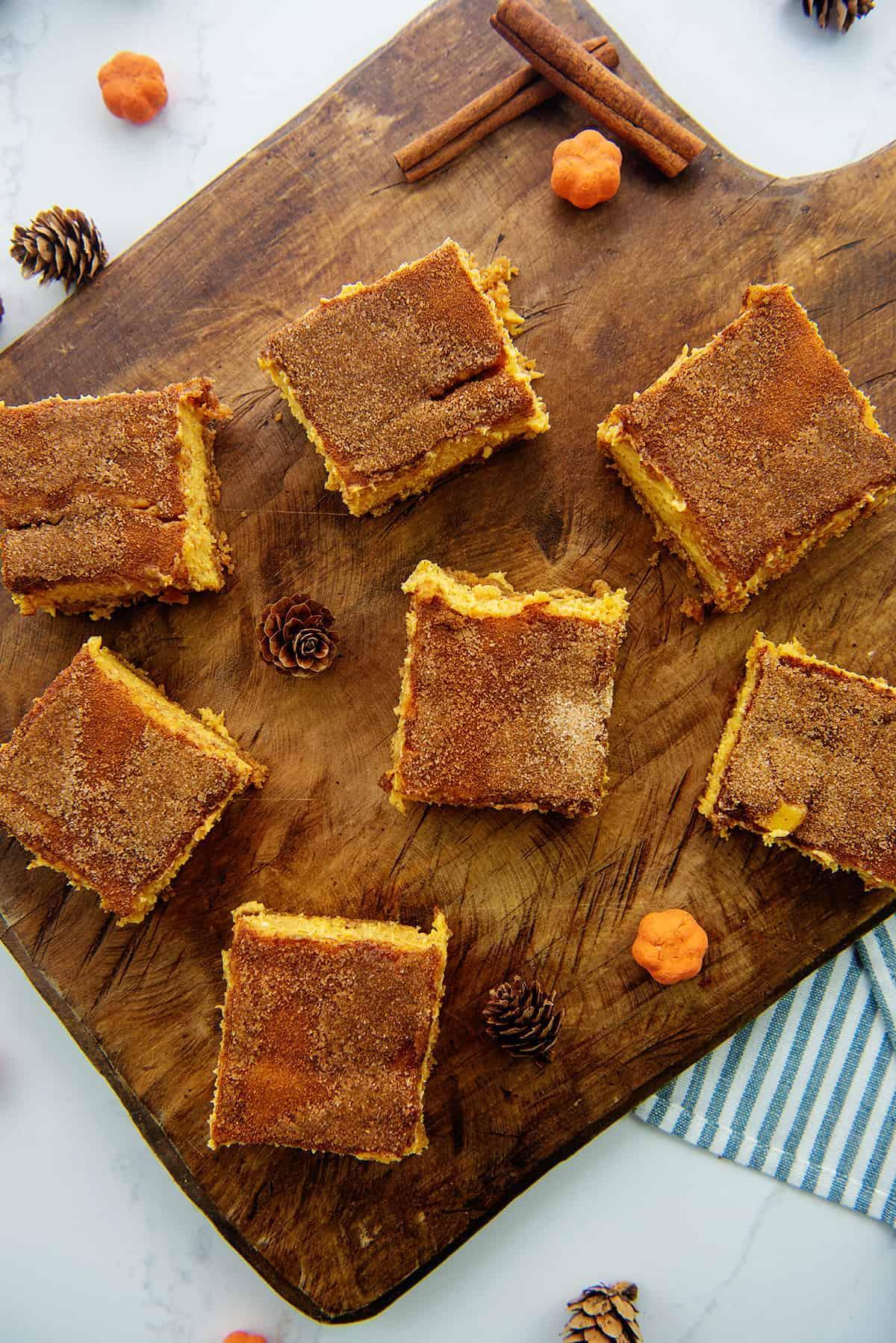 pumpkin cheesecake bars on wooden board.