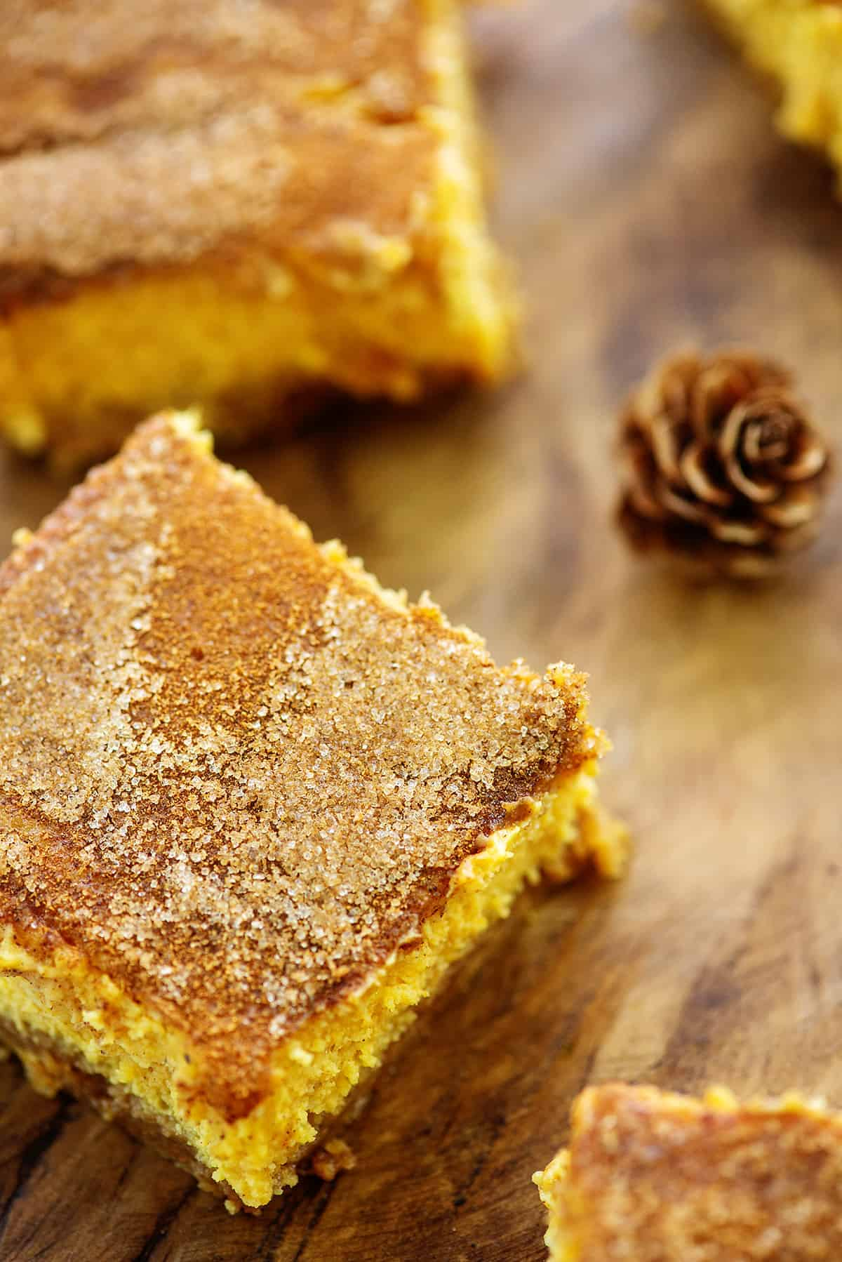 snickerdoodle pumpkin cheesecake bars on wooden cutting board.