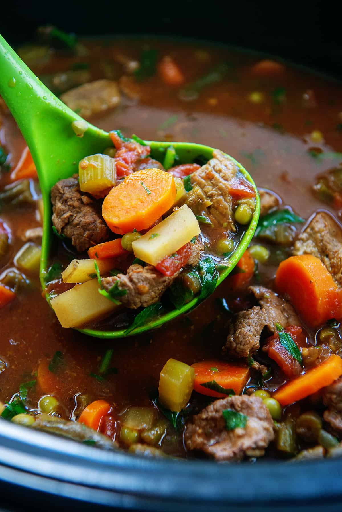 crockpot vegetable beef soup in a ladle.