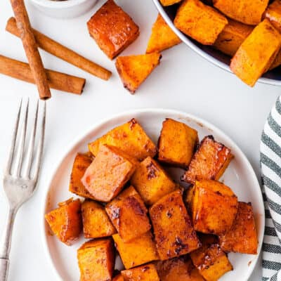 overhead view of honey cinnamon sweet potatoes on white plate.