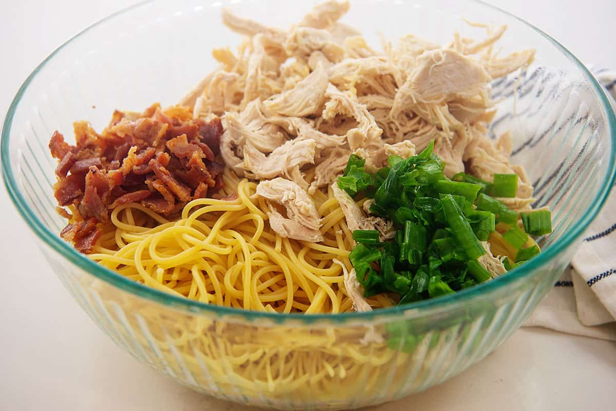 ingredients for chicken spaghetti in glass bowl.