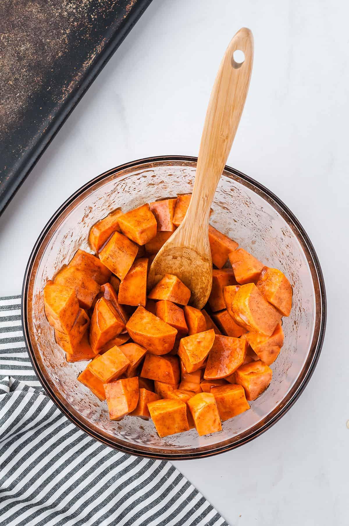 seasoned sweet potato cubes in glass bowl.